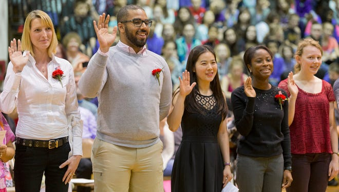 New citizens recite the Oath of Allegiance during a session of the Supreme Court of the State of New York held Wednesday afternoon at Boynton Middle School