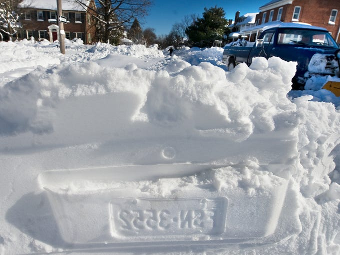 The imprint of a car license plate is left in the snow