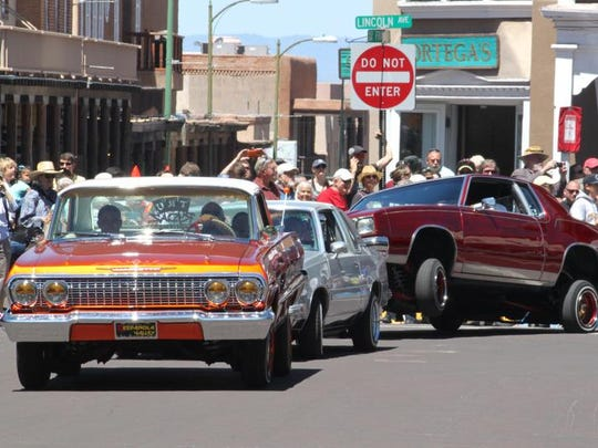 This May 22, 2016 photo shows lowriders parading around the historic plaza in Santa Fe, as part of the city's Lowrider Summer celebration. The New Mexico History Museum and the New Mexico Museum of Art also are hosting exhibitions highlighting the lowrider culture.