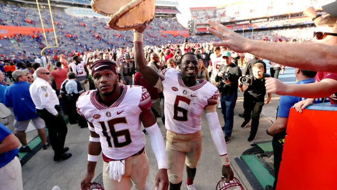 FSU's Jacob Pugh, left, walks with Matthew Thomas as he holds a gator head high in celebration of the Seminoles 38-22 win over Florida at Ben Hill Griffin Stadium in Gainesville on Saturday.