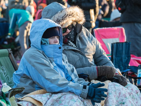 Two women attempt to stay warm while they await the launch of an Antares rocket launch at Wallops Flight Facility Visitor's Center on Saturday, Nov. 11, 2017.