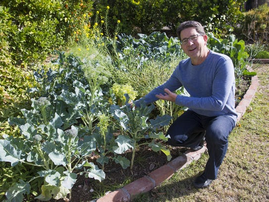 Greg Peterson, owner of The Urban Farm, kneels in his