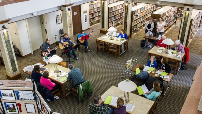 """Participants sing along to live music by the """"Acoustic Strings"""" trio during the """"memory cafe"""" event hosted by the Hartland Public Library on Friday, April 3, 2015. Oconomowoc will host a dementia caregiver resource fair on Sept. 20."""