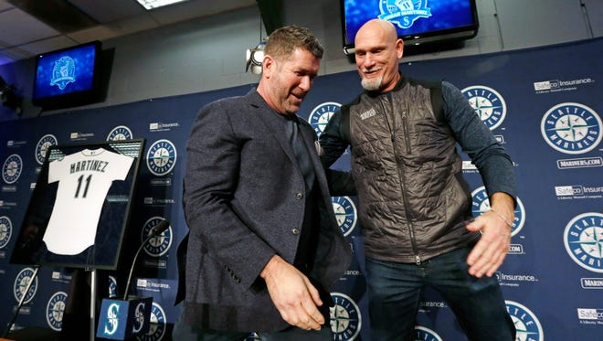 Seattle Mariners hitting coach Edgar Martinez (left) is greeted by former teammate Jay Buhner following Tuesday's news conference announcing the retirement by the team of Martinez's jersey No. 11 this August.