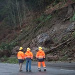 State department of transportation officials survey the scene of a mudslide obstructing the northbound lane of Interstate 5 near Woodland,, Was., Thursday, Dec. 10, 2015. Boulders, trees and dirt slid onto the highway in the day before following heavy rains. (Natalie Behring/The Columbian via AP) MANDATORY CREDIT
