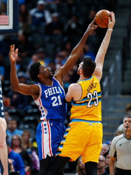 Philadelphia 76ers center Joel Embiid, left, reaches up to block a shot by Denver Nuggets center Jusuf Nurkic, of Bosnia, in the first half of an NBA basketball game Friday, Dec. 30, 2016, in Denver. (AP Photo/David Zalubowski)