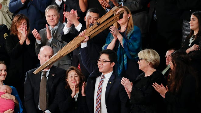 Ji Seong-ho, who escaped from North Korea, holds up his crutches after being acknowledge by President Donald Trump during Trump's address to a joint session of Congress on Capitol Hill in Washington, Tuesday. He was one of several people in the crowd Trump singled out during his State of the Union speech.
