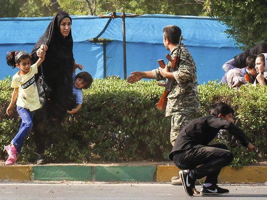In this photo provided by Fars News Agency, a woman takes her children to shelter as an army member tries to help them, during a shooting at a military parade.