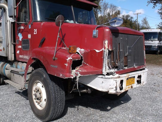 The front of a dump truck shows the damage it received