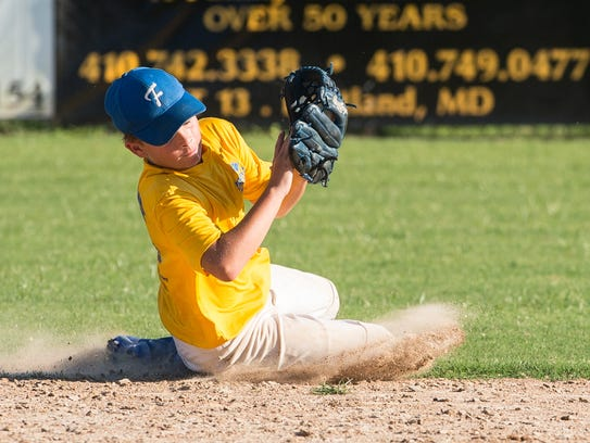 A Fruitland shortstop slides to catch the ball during