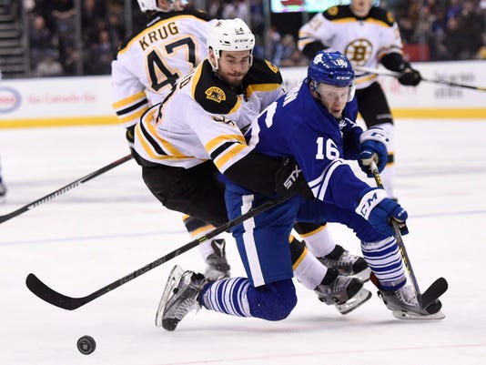 Boston Bruins' Adam McQuaid (54) picks up a holding penalty on Toronto Maple Leafs' Connor Brown (16) during second-period NHL game action in Toronto on Saturday, March 26, 2016. (Frank Gunn/The Canadian Press via AP) MANDATORY CREDIT