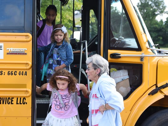 Students exit a bus for the first day of school at