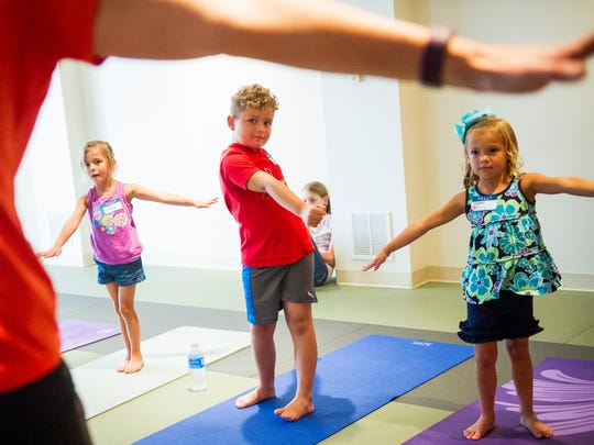 Olivia Brown 5, from left,  Max Carmona, 6, and Paisley Whetstine, 5, all of Evansville, follow yoga instructor Amy Stephen, also of Evansville, during Curious Adventure with Miss Amy, a children's yoga class offered at the Tri-State Athletic Club in Evansville, Sunday, Sept. 18, 2016. The club plans to offer children's yoga once a month.