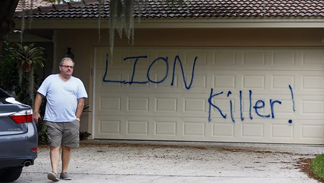 """Private Investigator for the Palmer family, Walter Zalisko, of Global Investigative group in Fort Myers walks out of the home Tuesday, Aug. 4, 2015, at the Marco Island home of dentist Walter J. Palmer. Zalisko said no vandalism was found inside. The home was discovered vandalized with the worlds """"LION Killer!"""" and littered with pigs feet drenched in hot sauce. Palmer, a Minnesota resident, is wanted in the killing of Zimbabwe's famous lion, Cecil, a lion who drew thousands of tourists and dollars annually. (Corey Perrine/Naples Daily News via AP)"""