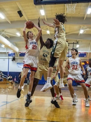 Eastern Randolph's Delonte Glover contests the shot of Randleman's Kaleb Mitchell last season. Glover and the Wildcats beat Wheatmore on Friday. [PJ Ward-Brown for The Courier-Tribune]