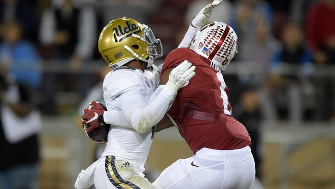 Stanford Cardinal receiver Francis Owusu (6) catches a 41-yard touchdown pass in the third quarter while defended by UCLA Bruins safety Jaleel Wadood (2) in the third quarter in a NCAA football game at Stanford Stadium.