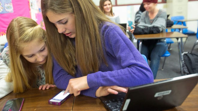 Students, Emme McCleary, 13, and Brenna Toshner, 13, use iPhones and an HP Notebook computer for a class assignment in their language arts class at Willis Junior High in Chandler, Ariz.