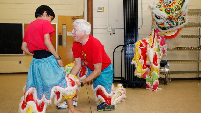 Mark Small helps is son, Haiden, 9, adjust his costume before performing the Lion Dance January 24, 2017, at Montfor Rec Center.