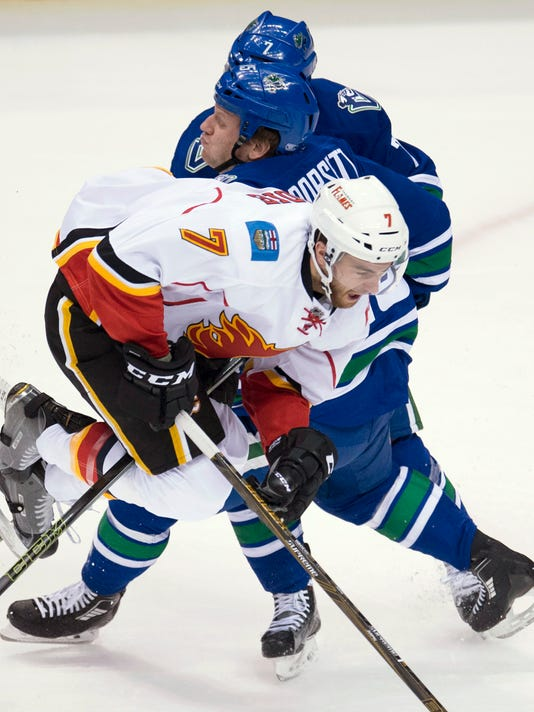 Calgary Flames defenseman T.J. Brodie (7) collides with Vancouver Canucks right wing Derek Dorsett (15) during the first period of an NHL hockey game Saturday, Feb. 6, 2016, in Vancouver, British Columbia. (Jonathan Hayward/The Canadian Press via AP)
