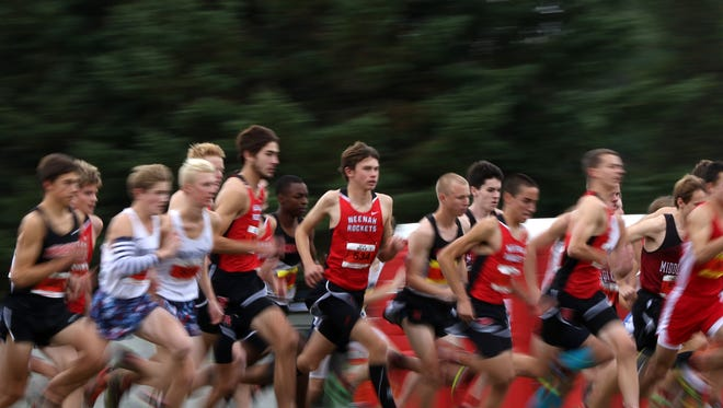Runners zoom by as they kick off the D1 tournament at the WIAA State Cross Country competition at the Ridges Golf Course in Wisconsin Rapids, Wis., October 29, 2016.