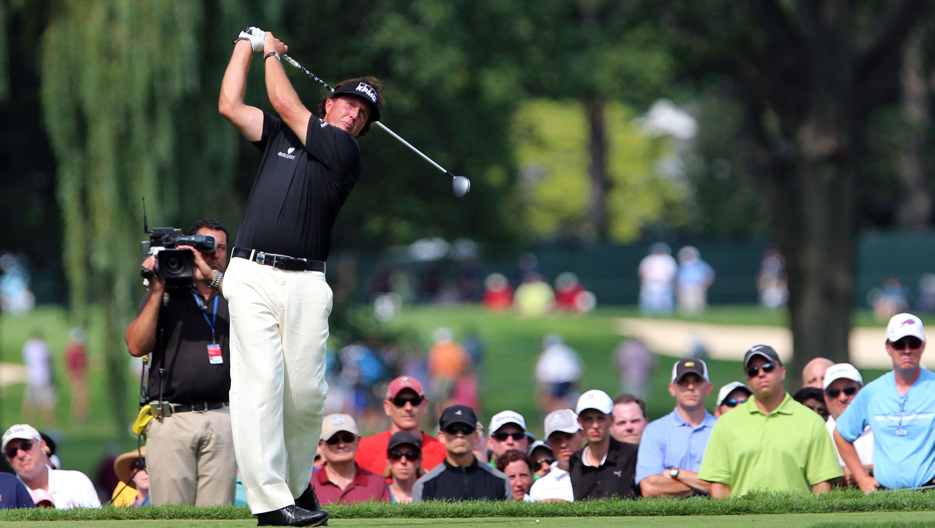 Phil Mickelson tees off on the 9th green during the first round of the 95th PGA Championship at Oak Hill Country Club.