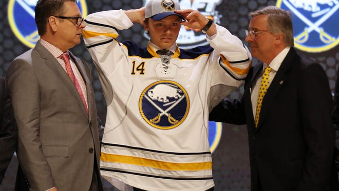 Sam Reinhart puts on a team cap after being selected as the number two overall pick to the Buffalo Sabres in the first round of the 2014 NHL Draft at Wells Fargo Center.