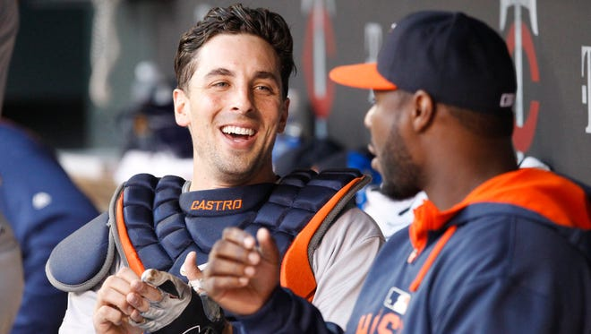 In this Aug. 28, 2015, file photo, Houston Astros catcher Jason Castro laughs with a teammate in the dugout before a baseball game against the Minnesota Twins in Minneapolis. The Twins signed Castro to a three-year, $24.5 million contract.
