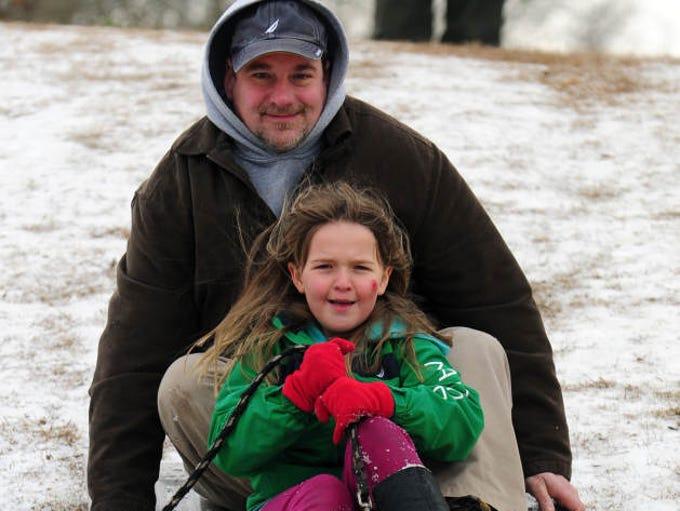 Aaron and Chloe, 7, Brackett sled down a hill Wednesday near Court Street in downtown Hattiesburg.