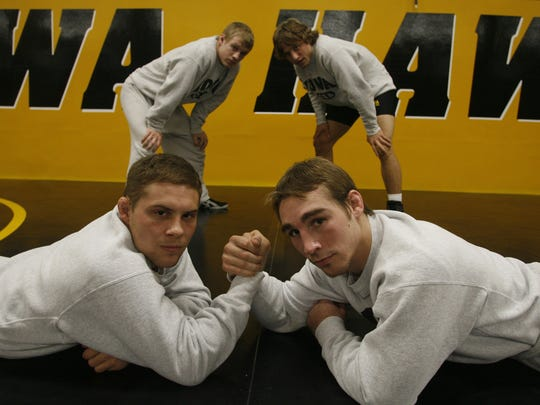 Joe Slaton, left, and Daniel Dennis, right, lock arms as Dan Leclere, back left, and Alex Tsirtsis stand behind them during the Iowa Wrestling Media Day in 2008.
