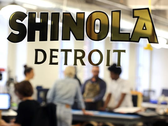 Designers for leather goods can be seen behind the Shinola Detroit sign at their factory in Detroit.