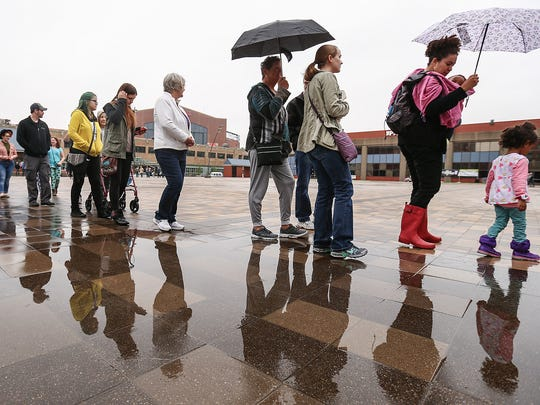 People wait in line at the Pan Am Pavilion to enter VegFest on Saturday. Thunderstorms and heavy rain caused several cancellations, such as Race for the Cure, for the first time in its 26-year history, and the Indy Humane Society's Mutt Strut at Indianapolis Motor Speedway.