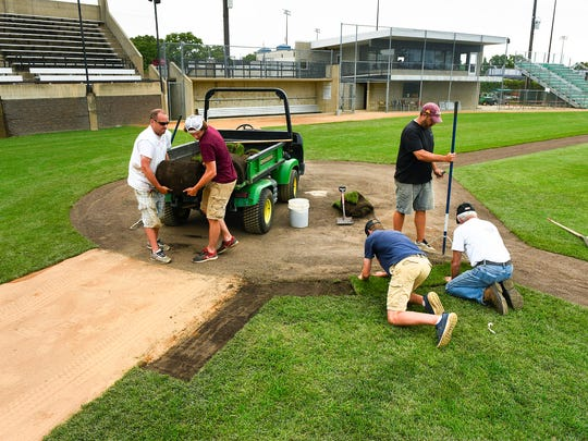 Grounds crew members prepare for a state baseball tournament Monday, June 12, 2017 at the MAC's Dick Putz Field.