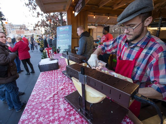 Virgil Walters, Chicago, serves up Swiss-German raclette cheese that gets melted under a flame, at Carmel's Christkindlmarkt, Wednesday, Nov. 29, 2017.