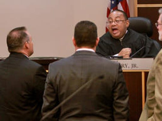 Judge Belvin Perry talks with attorneys during the