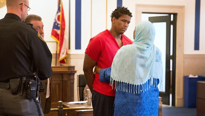 Rukiye Abdul-Mutakallim, 66, hugs and then speaks quietly with Javon Coulter, 16, during his plea agreement in Judge Megan E. Shanahan's courtroom. Abdul-Mutakallim had just finished publicly speaking to Coulter. She spoke of forgiveness and asked to be part of Coulter's life. Coulter was 14 when he was charged, along with another teen, in the shooting death of Rukiye's son, Suliman Ahmed Abdul-Mutakallim, 39, on June 28, 2015. He was bound over as an adult. Abdul-Mutakallim was shot in the head as he walked home with White Castle in South Cumminsville. He died the following day. Coulter will serve 20 years for involuntary manslaughter with gun specification and aggravated robbery with gun specification. The second teen, Valentino Pettis, also took a plea and will serve 14 years. After Rukiye spoke, Coulter apologized for causing the death of her son.