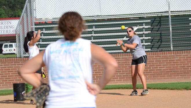 Former University Academy of Central Louisiana softball coach Meagan Pearson (right) hits a ball at practice this past season. Pearson, a former Louisiana College standout, has been hired as an assistant at Louisiana Tech.