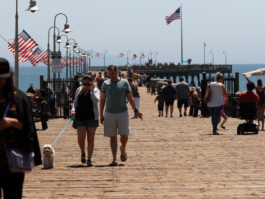 Visitors walk the Ventura Pier. The pier and Ventura's beaches attract tourists, especially in the warm summer months.