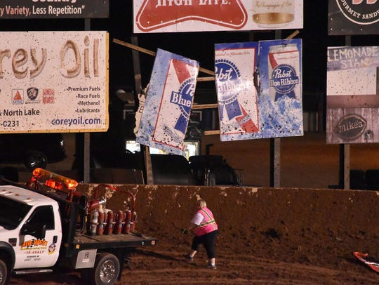 A woman works near a billboard broken when Jason Johnson's World of Outlaws sprint car flipped out of the track at Beaver Dam Raceway on Saturday night.
