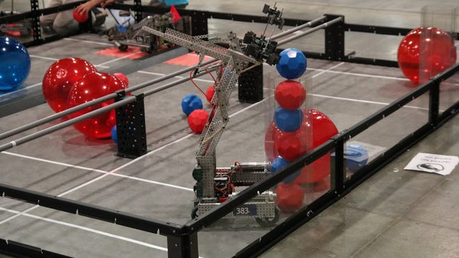 A robot built by Delaware students races to stack balls in a container during a competition at the National Technology Association conference.