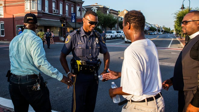 Community members thank police Officer Dakevis Howard following a vigil and march through Middletown on Thursday evening. About 100 Middletown residents gathered in the town's Cochran Square for a prayer vigil and unity march.