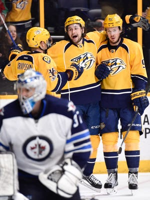 Predators center Ryan Johansen (92) celebrates his goal past Jets goalie Connor Hellebuyck (37) with teammate Viktor Arvidsson (38) and  Filip Forsberg (9) during the third period Monday. The Predators have points in four consecutive games (2-0-2) after defeating the Jets.