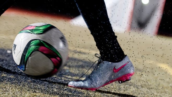 Photo illustration of rubber particles being kicked up at the St.Xavier High School soccer field. The Kentucky Players Academy was practicing there.16 February, 2016