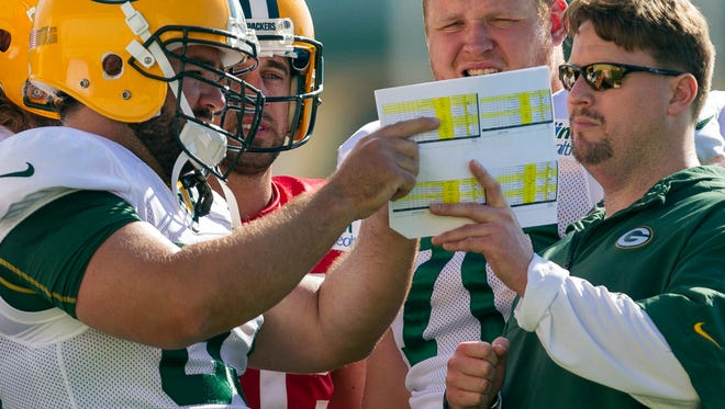In this July 28, 2012, file photo, then-Green Bay Packers quarterbacks coach Ben McAdoo, right, talks with center Jeff Saturday (63), quarterback Aaron Rodgers (12) and offensive guard T.J. Lang (70) talk during training camp in Green Bay, Wis. McAdoo will catch up with old friends when he returns to Lambeau Field to coach the New York Giants in a game against the Packers on Sunday.