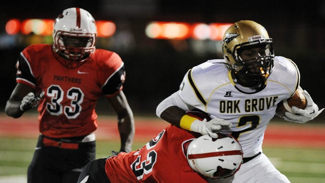 Oak Grove's Jordan Duncan is wrapped up by Petal's Taylor Wilson as C.J. Johnson(33) closes in.