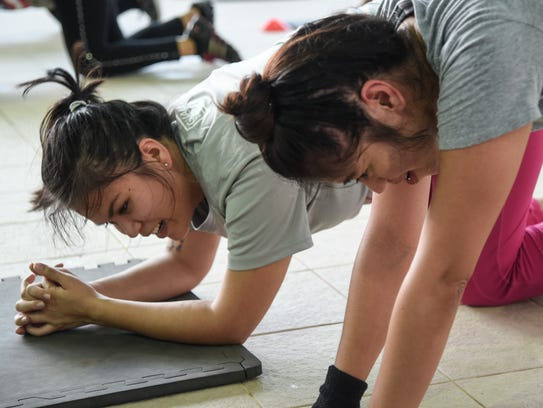 Gennie-May Whitt, right, enjoys a partner plank exercise