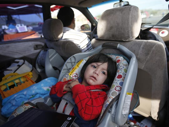 Jaden Rosales, 1, of Phoenix, waits with his parents