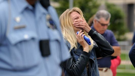 Kristina Rodeman-Brower, cousin of deceased Lansing Fire Department firefighter Dennis Rodeman, cries during a prayer for the fallen firefighter during the emotional ceremonies honoring Rodeman and also marking the 9/11 terrorist attacks on Sept. 11, 2015.