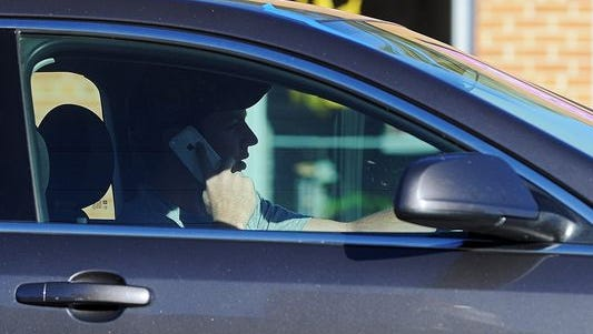 A driver uses his mobile phone while stopped at the intersection of Cliff Avenue and 26th Street Monday, Oct. 12, 2015, in Sioux Falls.