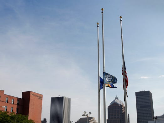 Flags fly at half-mast over the city skyline outside the Public Safety Building Friday in honor of slain Rochester Police Officer Daryl Pierson, who was killed in the line of duty Wednesday night, Sept. 3.  Gov. Andrew Cuomo ordered flags be flown across the state in honor of Officer Pierson.