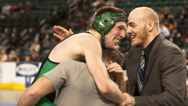 Brick Memorial's Alec Donovan (left) jumps into the arms of Mustangs assistant coach Dean Albanese and grabs Brick Memorial head coach Mike Denver's hand after winning the 145-pound state championship Sunday at Boardwalk Hall.